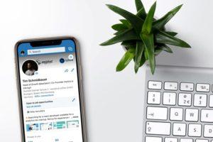 LinkedIn profile on phone next to laptop