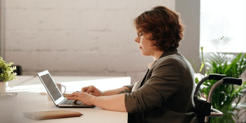 Employee working in wheelchair on laptop