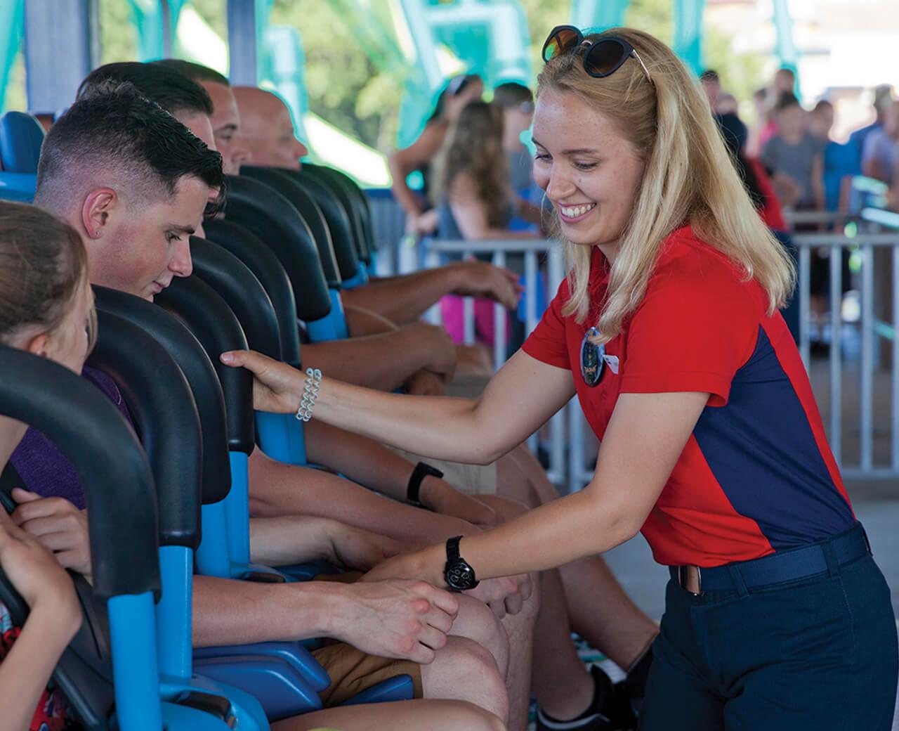 Cedar fair employee securing people on a roller coaster
