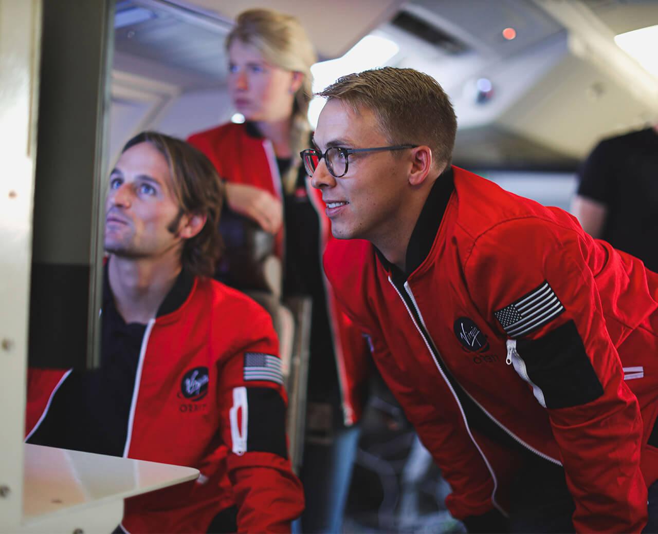 3 Virgin Orbit scientists looking at a computer screen